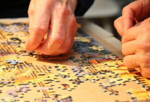 hands working a jigsaw puzzle